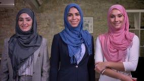 Tre femmine arabe sorridenti che indossano il hijab, rosa, blu e grigio sono stanti ed esaminanti la macchina fotografica, nell'u stock footage