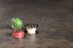 Tre fili bianco di corrispondenza di cucito delle bobine rosa, verde e Fotografie Stock Libere da Diritti