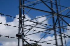 Tre fili di filo spinato con la torre di comunicazioni nel fondo Fotografia Stock