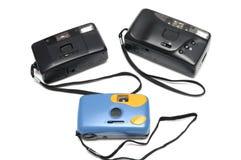Tre filmkameror med svarta handledremmar Två är svart, medan annat är blått i färg royaltyfri fotografi