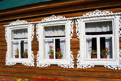 Tre finestre di una casa di legno della contea decorata dalle strutture bianche Immagini Stock