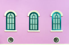 Tre finestre incurvate verdi sulla parete rosa Fotografie Stock