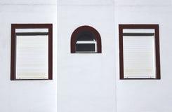 Tre finestre su una parete fotografia stock