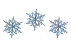 Tre fiocchi di neve isolati su fondo bianco Immagine Stock