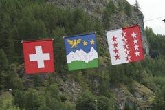 Tre flaggor av Schweiz, Wallis och Val D ` Hérens bredvid de framme av ett berg och träd Royaltyfria Foton
