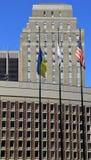 Tre flaggor framme av affärsbyggnader Royaltyfria Foton