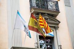 Tre flaggor på gammal Barcelona byggnad Arkivbild