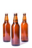 Tre flaskor av iskallt öl som isoleras på vit Arkivfoton
