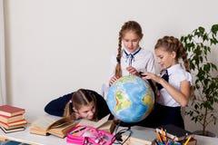Tre flickaskolflickor på kursen av geografi med ett jordklot i skola arkivbilder