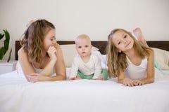 Tre flickasystrar i morgonen i sovrummet på sängleken arkivbilder