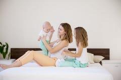 Tre flickasystrar i morgonen i sovrummet på sängleken royaltyfri fotografi