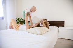 Tre flickasystrar i morgonen i sovrummet på sängleken royaltyfria bilder