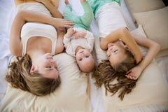 Tre flickasystrar i morgonen i sovrummet på sängleken royaltyfria foton