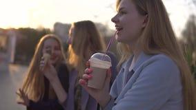 Tre flickav?nner som har gyckel p? aftonen broadway ?ta glass och att dricka den nya milkshaken f?r is och att tugga bubblan arkivfilmer