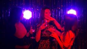 Tre flickor dricker vin, meddelar och dansar på ett parti arkivfilmer