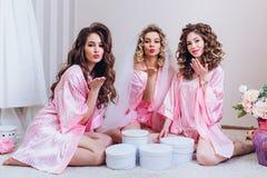 Tre flickor firar ett ungkarlparti eller f?delsedag royaltyfri fotografi