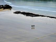 Tre flickor går den kala foten över den Newquay stranden, i Cornwall, i slutet av dagen, som tidvattnet avgår arkivbilder