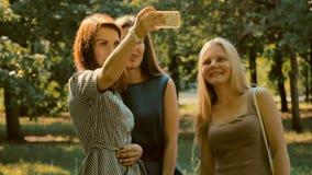 Tre flickor går fotograferat lager videofilmer