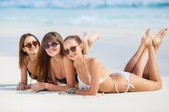 Tre flickor i bikini som solbadar att ligga på sanden Arkivbild