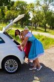 Tre flickor i Dirndl och henne bil Arkivbilder
