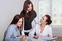Tre flickor i formell kläder som undertecknar affärsdokument Arkivbild