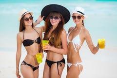 Tre flickor i hattar som dricker fruktsaft nära havet Arkivbild