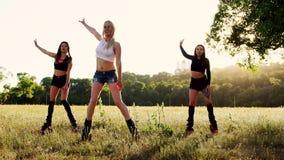 Tre flickor i kängor på vårar utför feta bränningövningar i grupputbildning stock video