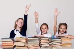 Tre flickor i klassrumet, lyftte ett svar för hand upp till arkivbild