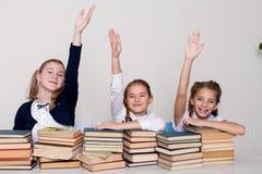 Tre flickor i klassrumet, lyftte ett svar för hand upp till royaltyfria bilder