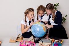 Tre flickor i klassrumet som studerar geografijordklotet av planetjord royaltyfria bilder
