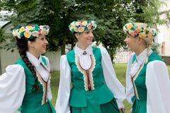 Tre flickor i lettiska folk dräkter på naturen Royaltyfri Bild