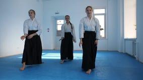 Tre flickor i svart hakama övar Aikidoförehavanden på kampsportutbildning lager videofilmer