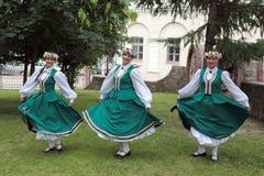Tre flickor i traditionell klänningdans i gräset Arkivbild
