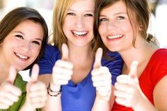 Tre flickor med tum upp Royaltyfri Bild