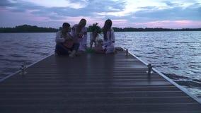 Tre flickor och en grabb med en gitarr sitter på pir lager videofilmer