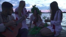 Tre flickor och en grabb med en gitarr sitter på pir arkivfilmer