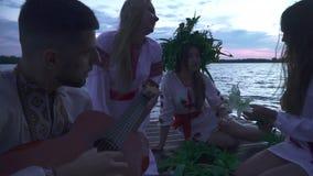 Tre flickor och en grabb med en gitarr sitter på pir stock video