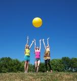 Tre flickor play med den gula bollen Royaltyfri Fotografi