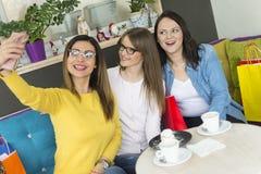 Tre flickor sitter i en kaka shoppar och fotograferar sig med en smartphone arkivfoto