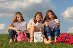 Tre flickor sitter på gräs och läser något Arkivbilder