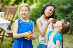 Tre flickor som äter frukt i trädgård royaltyfri bild