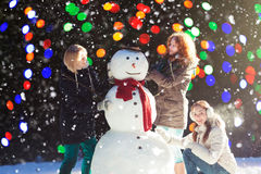 Tre flickor som bygger en snögubbe Royaltyfria Foton