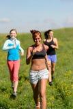Tre flickor som joggar den sluttande sommarängen Arkivfoto