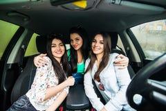 Tre flickor som kör i en bil och har gyckel royaltyfri fotografi