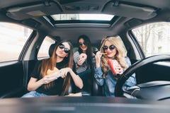 Tre flickor som kör i en bil och har gyckel som äter snabbmat i loppvägtur fotografering för bildbyråer
