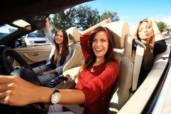 Tre flickor som kör i en konvertibel bil och har gyckel arkivfoton