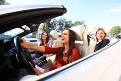 Tre flickor som kör i en konvertibel bil och har gyckel arkivbilder