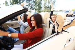 Tre flickor som kör i en konvertibel bil och har gyckel royaltyfri fotografi