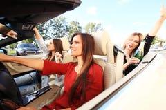 Tre flickor som kör i en konvertibel bil och har gyckel arkivfoto