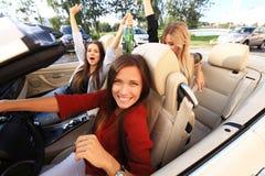 Tre flickor som kör i en konvertibel bil och har gyckel royaltyfri foto
